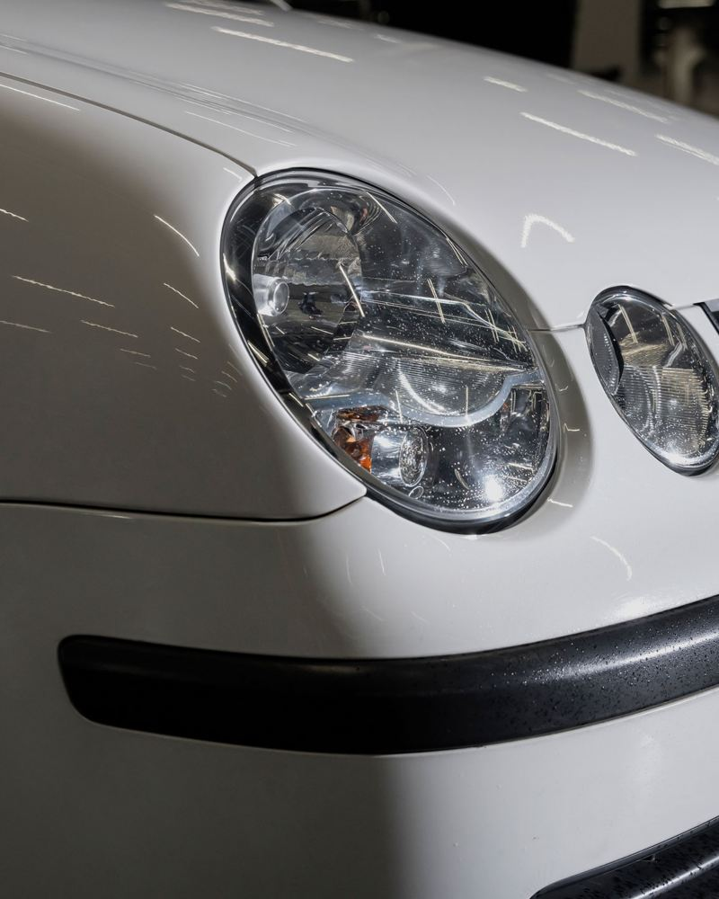 Ein VW Servicemitarbeiter tauscht eine Bremsscheibe an einem Auto aus – Volkswagen Teile