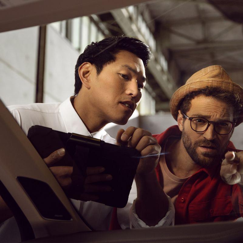 Un addetto VW Service controlla il parabrezza di un'auto assieme a un cliente.
