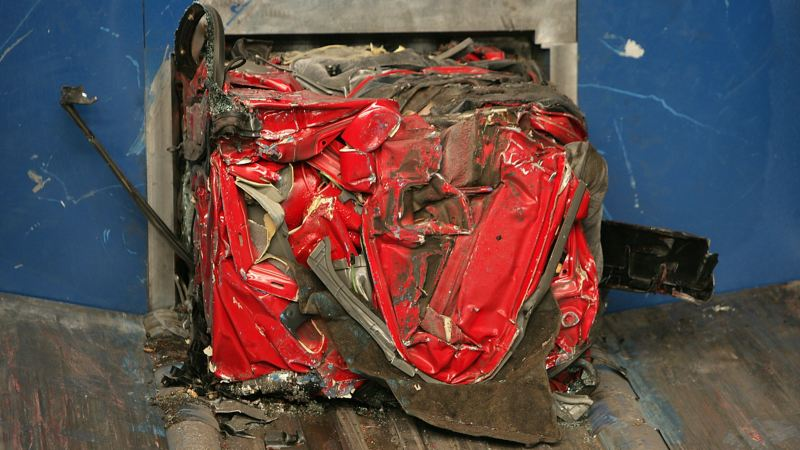 A compressed red car prepared for the shredder