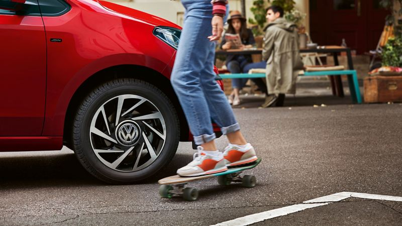 A woman on a skateboard drives past a red VW up!