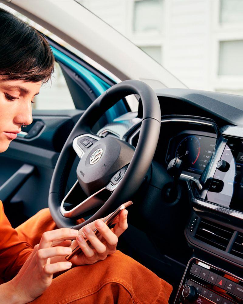 VW T-Cross Interieur mit Frau Blick auf Smartphone gerichtet