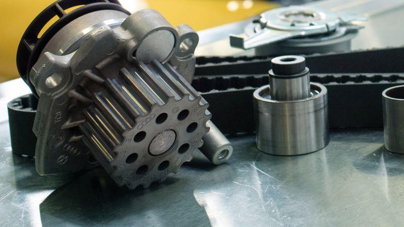 Tay của một nhân viên dịch vụ VW vặn vào khoang động cơ của chiếc VW