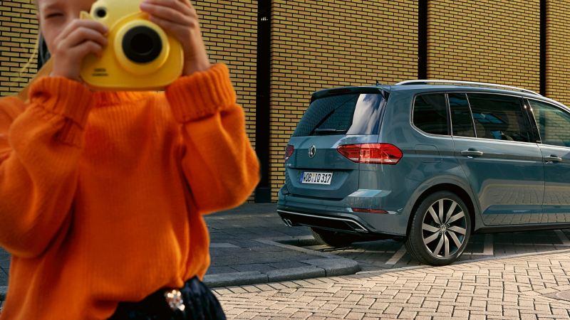 Un enfant avec un Viewmaster se tient debout devant une Volkswagen dont on voit les pneus