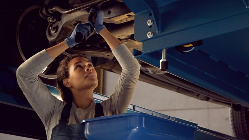 Mechanikerin erledigt Arbeiten am VW – Wartung & Inspektion