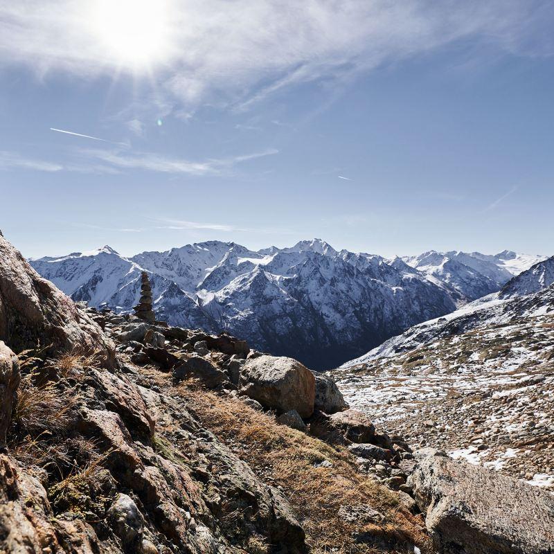 Un uomo affacciato su una terrazza su un tetto in collina ammira i tetti di una città di mare.