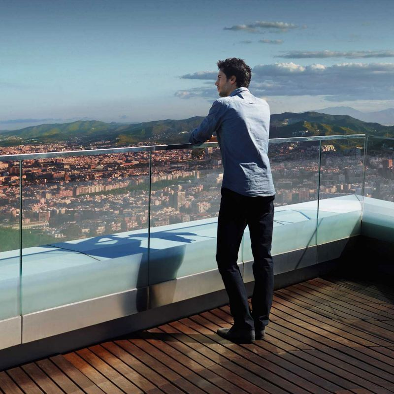 Un uomo guarda il panorama di una città dal tetto di un edificio