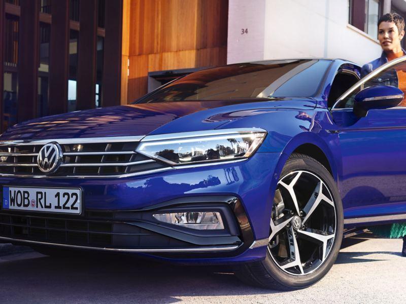 Una ragazza sta salendo a bordo della sua Volkswagen blu.