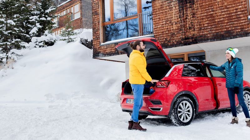A person picks up a snowboard from the ski and snowboard holder of his silver VW car with winter tyres in a snowy landscape