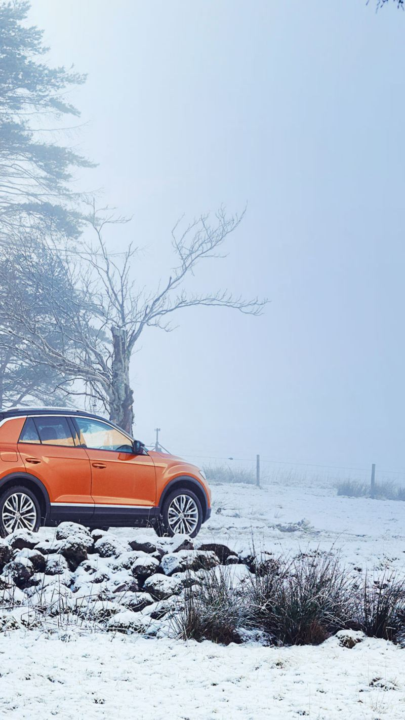 An orange VW car with winter tyres in a snowy landscape in front of a house