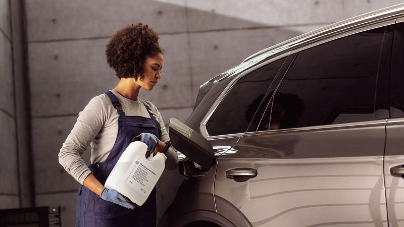 A VW service employee refills AdBlue® into a Volkswagen