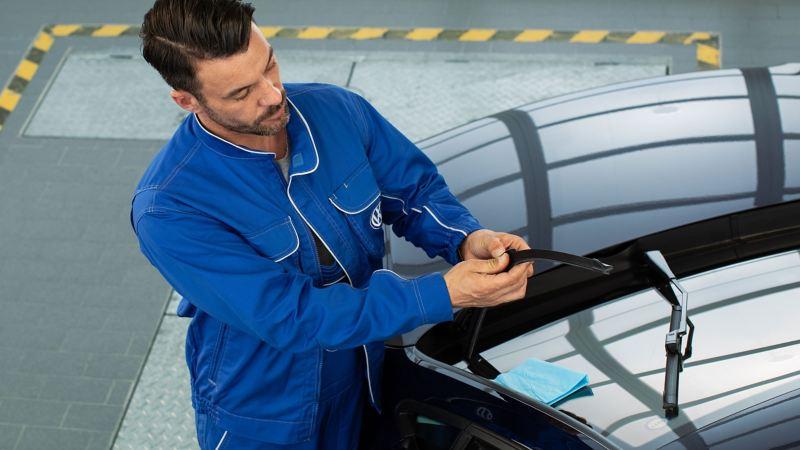 Un Réparateur Agréé Volkswagen répare des balais d'essuie-glace sur une Volkswagen