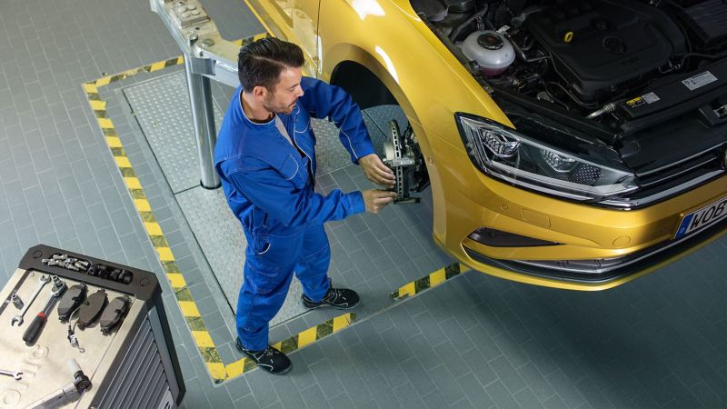 A VW service employee checks a checklist in a workshop – important customer information
