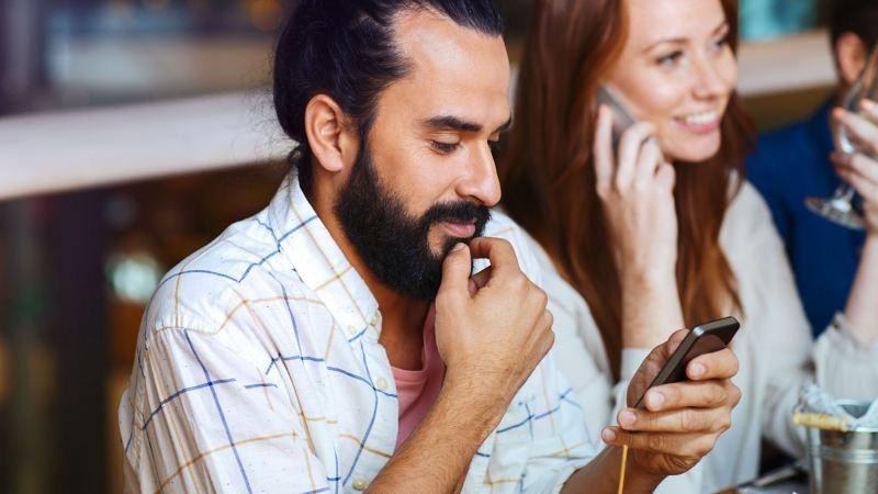 Ein Mann sitzt in einem Café und interagiert mit seinem Smartphone – Customer Interaction Center