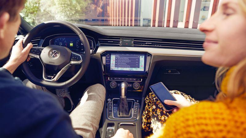 Ein Pärchen sitzt in ihrem VW Auto und unterhält sich – Customer Interaction Center