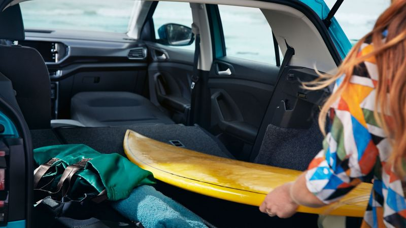 A woman stows her surfboard into her spacious VW car with folded down seats