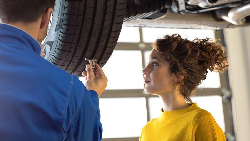 Kundin und Mechaniker bei Reifeninspektion