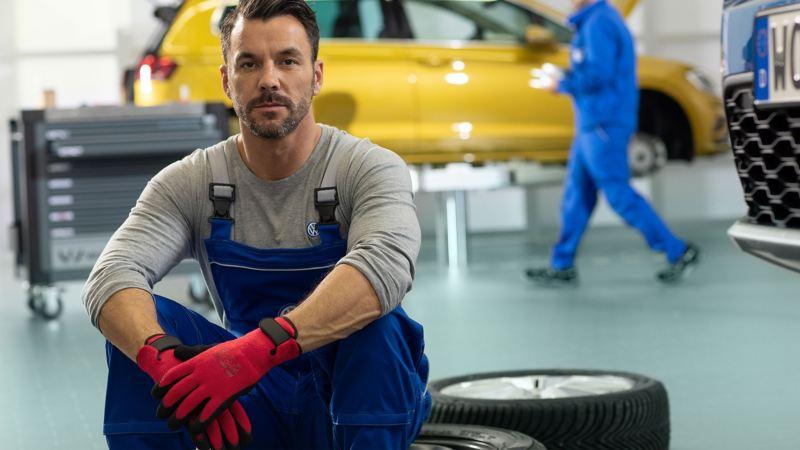 Mechaniker sitzt bei Reifen