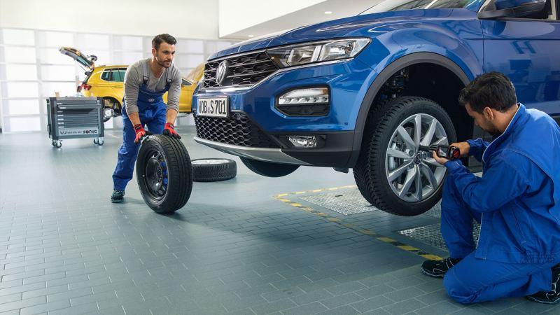 Mechaniker montieren neue Räder und Reifen