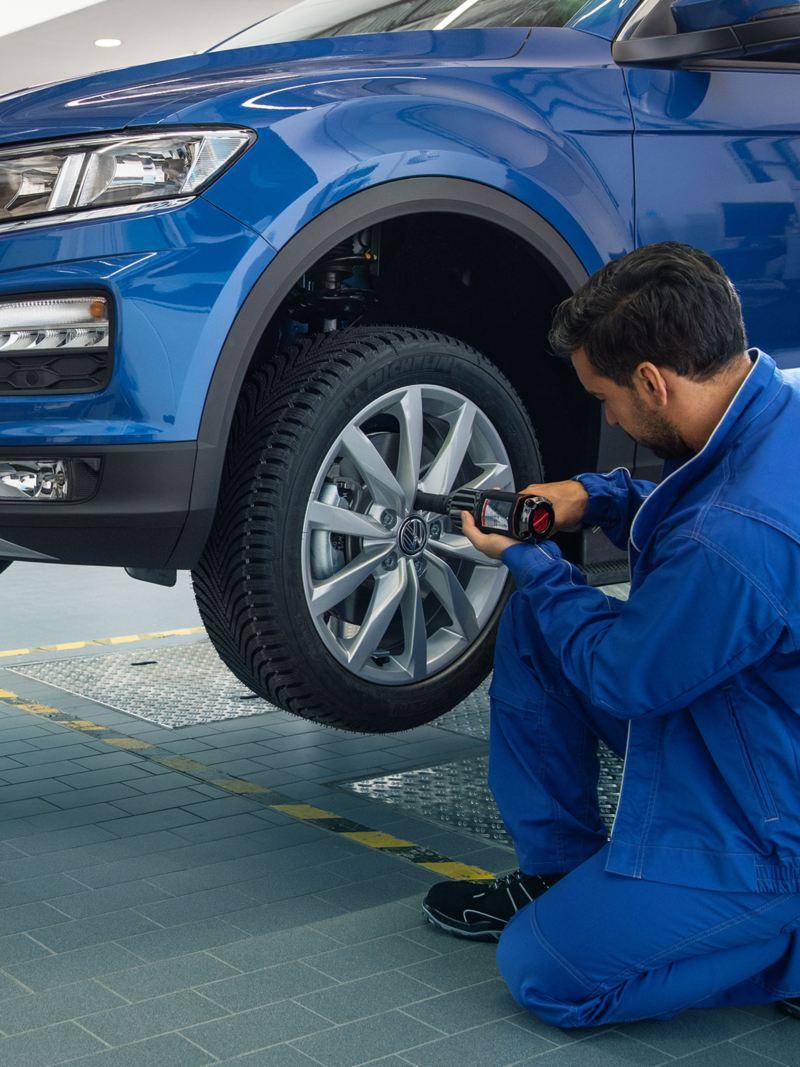 Zwei VW Servicemitarbeiter arbeiten zusammen an einem blauen VW Tiguan in einer Werkstatt