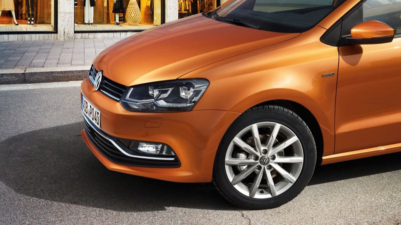The side view of an orange Volkswagen Polo 5 standing in front of a shop