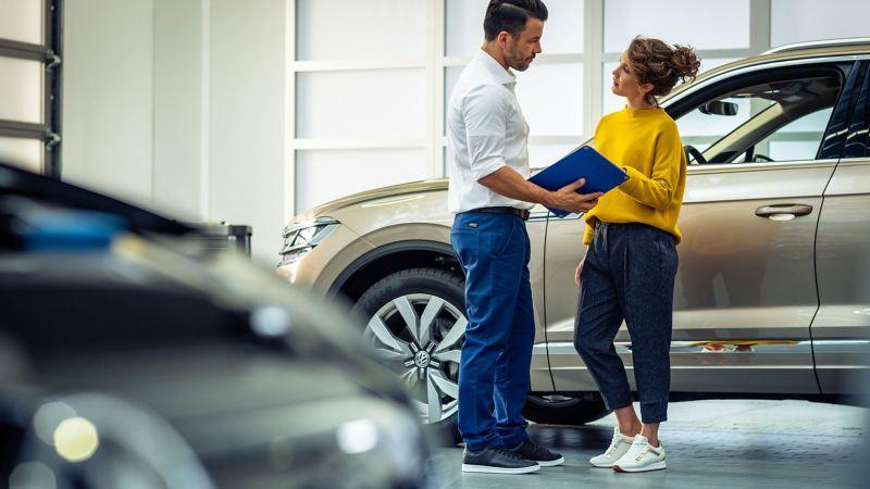 Une femme et un Réparateur Agréé discutent de l'entretien de son véhicule.