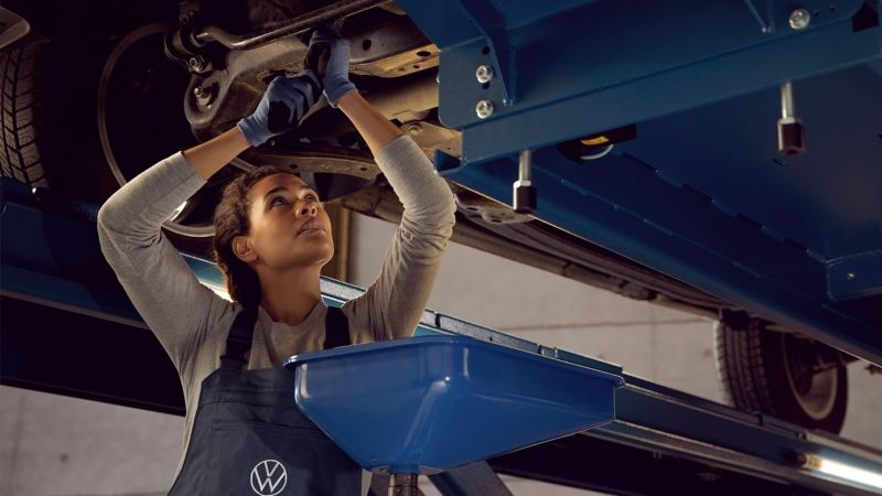 A VW service employee makes an oil change in flexible or fixed service on a VW car