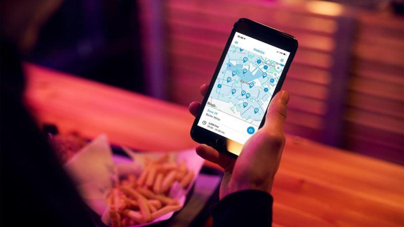 Frau schaut auf ihr Smartphone mit der We Park App