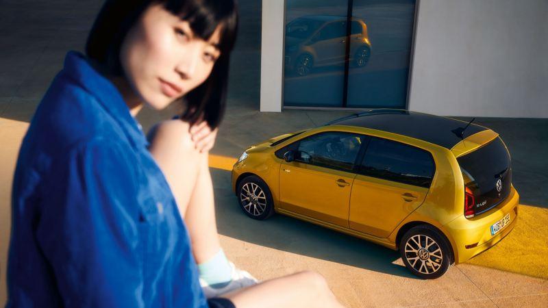 Eine Frau sitzt vor einer VW Werkstatt mit einem gelben Volkswagen e-up!