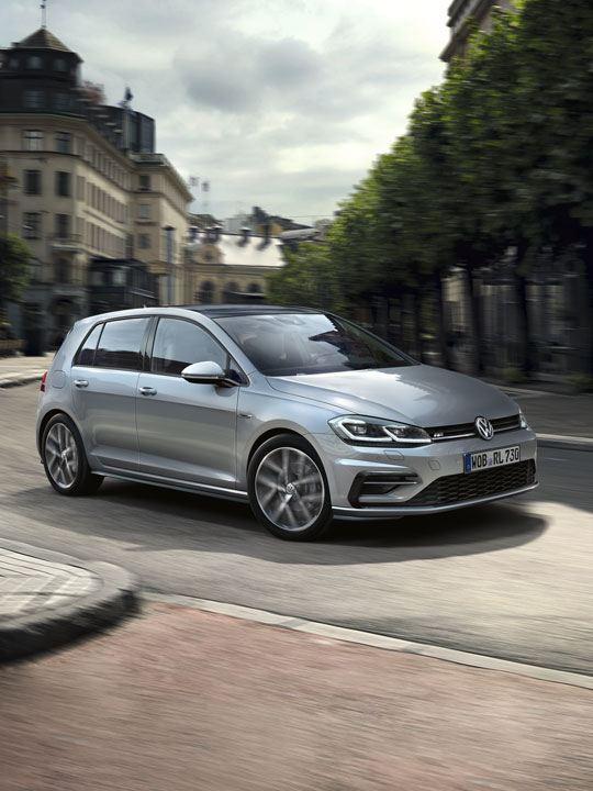 Volkswagen Golf plateado en la ciudad girando en una curva