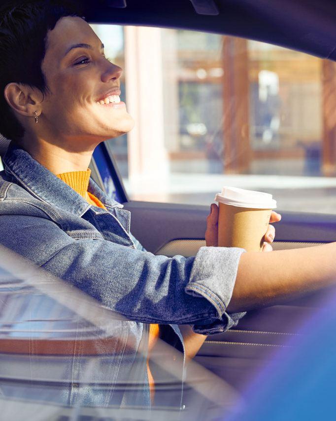 Mujer joven conduciendo y tomando un café
