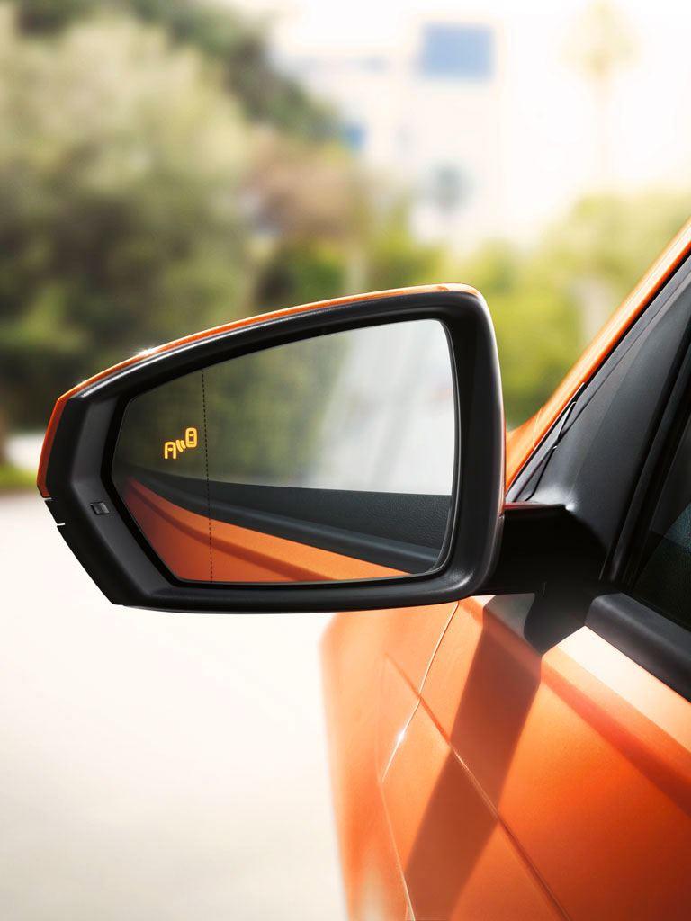 Detector de ángulo muerto en el retrovisor de un Volkswagen Polo naranja