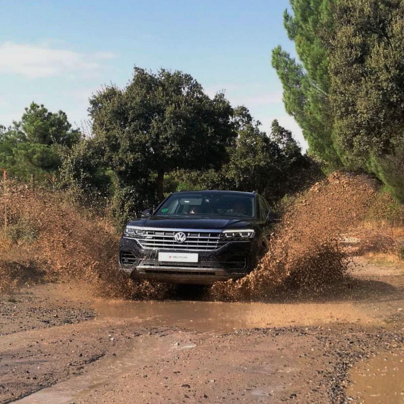 Volkswagen Touareg circulando por un camino con barro