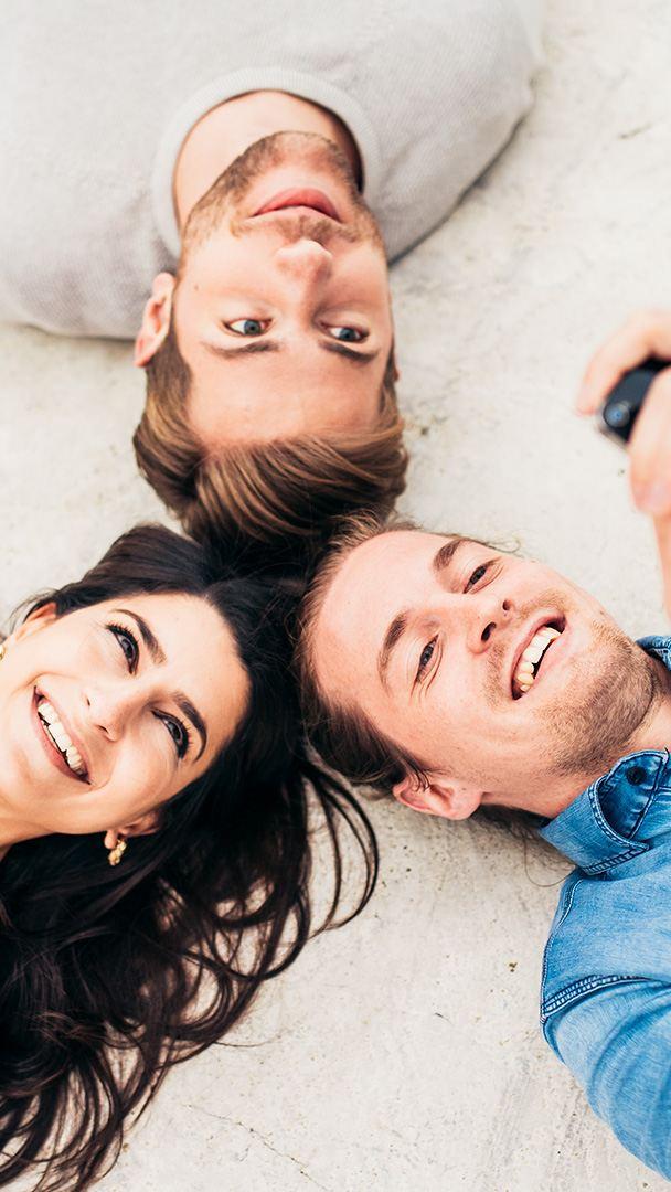 Drei junge Menschen amüsieren sich mit ihren Smartphones