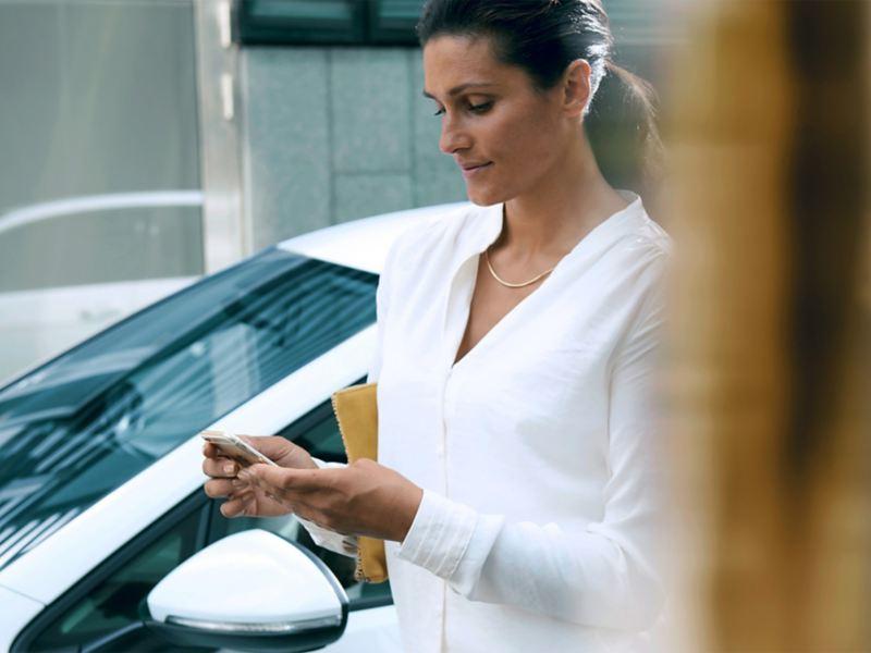 Eine Frau neben einem Fahrzeug schaut auf ihr Smartphone