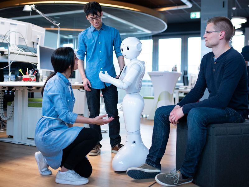 Eine Frau und zwei Männer arbeiten mit einem humanoiden Roboter