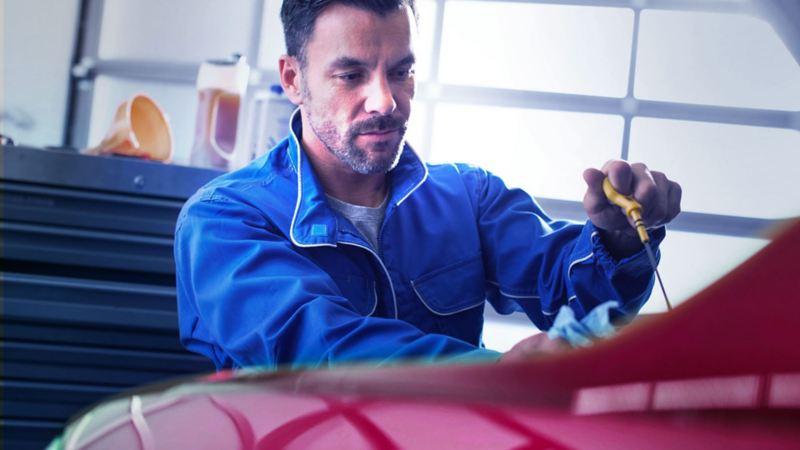 Un meccanico di VW Service sta controllando il livello dell'olio di un veicolo Volkswagen in officina.