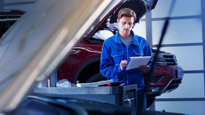 Un meccanico di Volkswagen Service intento a compilare una check list.
