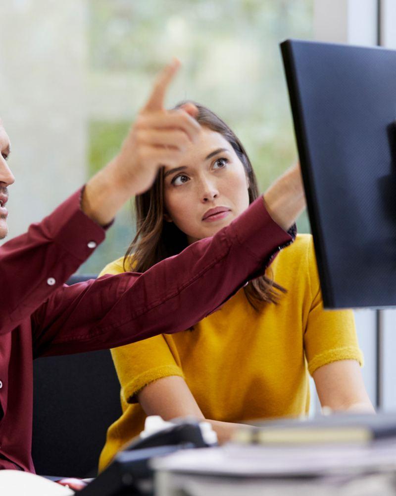 Eine Frau und ein Mann schauen gemeinsam auf einen Bildschirm