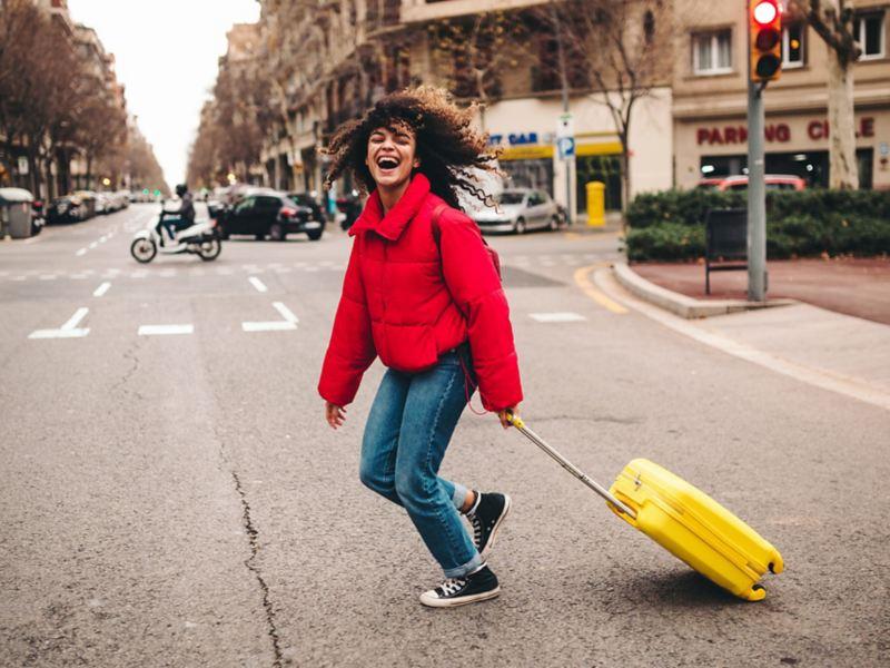 Eine Frau überquert mit ihrem Koffer die Straße