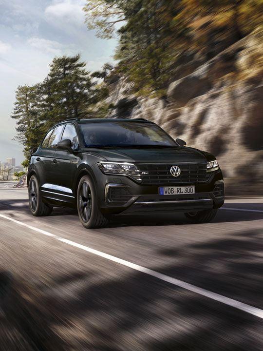 Volkswagen Touareg negro avanzando en la carretera frente a un paisaje