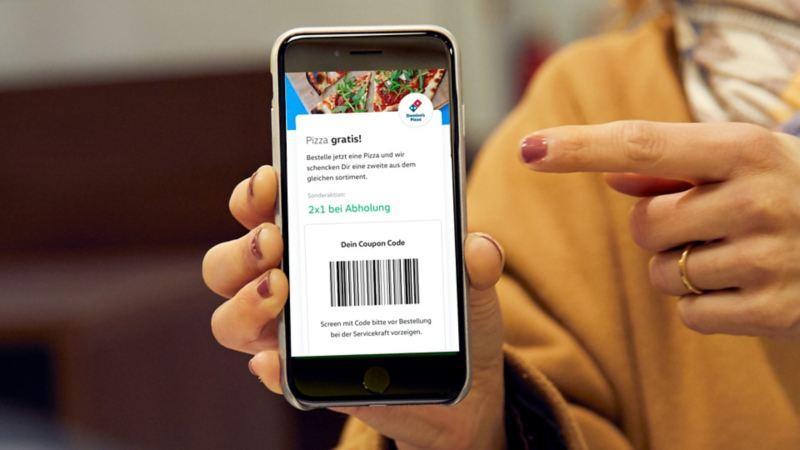 Junge Frau löst einen Gutschein mit ihrem Smartphone ein.