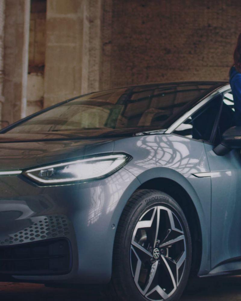 Donna appoggiata a ID.3 VW che aspetta