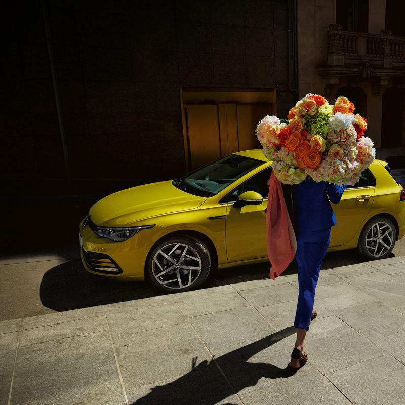 Kvinna med blommor i famnen går framför Volkswagen Nya Golf