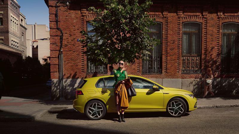 Nya golf parkerad vid vägkant, en kvinna går framför