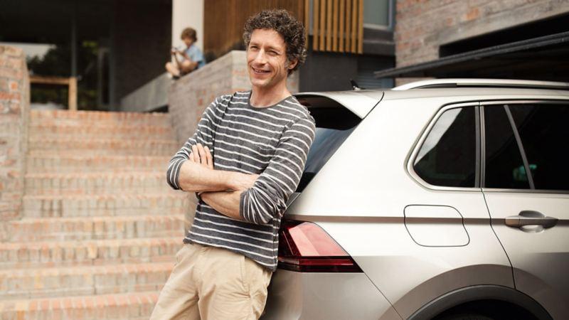 Mann lehnt an seinem Neuwagen mit Garantieverlängerung