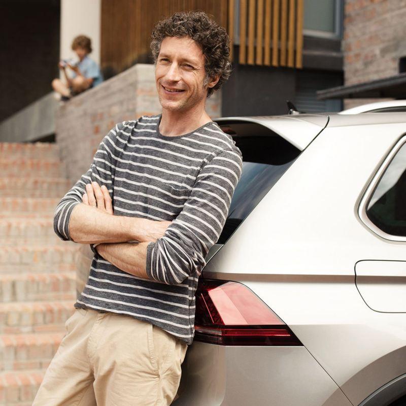 Volkswagen Tiguan kuvattuna läheltä, iloinen henkilö nojaa autoa vasten