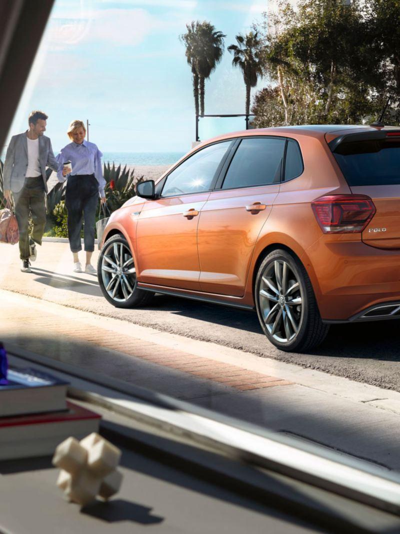 Pareja caminando en dirección a un Volkswagen Polo visto desde una ventana