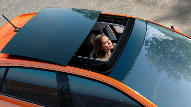Chica mirando cómo se abre el techo panorámico de su Volkswagen Polo