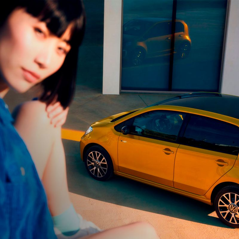 Chica joven desenfocada mirando a la cámara frente a un e-up! amarillo
