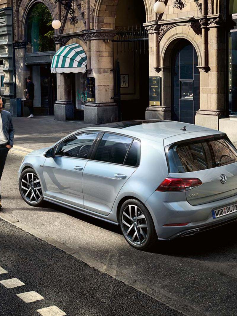 Volkswagen Golf aparcado en la ciudad, hombre joven caminado delante